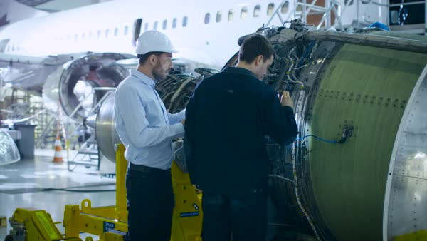 Aircraft maintenance engineer and mechanic inspecting and working on airplane jet engine in hangar Royalty-free stock video