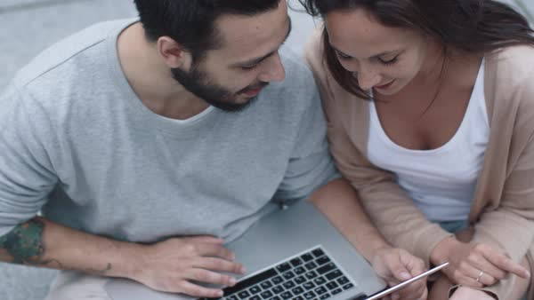 Young woman and man are using laptop outdoors. Royalty-free stock video