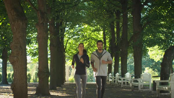 Young Man and Woman Moving Towards Camera During Morning Run in Park. Royalty-free stock video