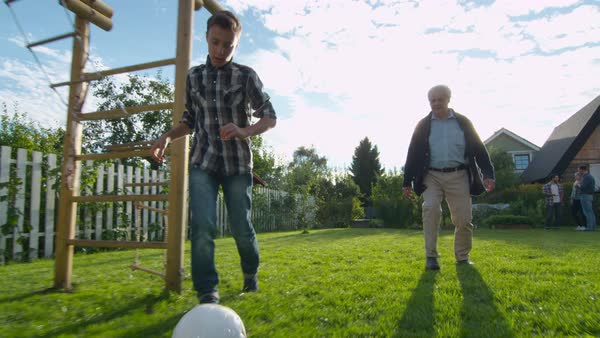 Grandfather and Grandson Play Football in the Backyard. Royalty-free stock video