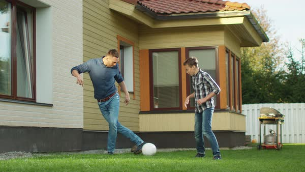Father and Son Playing With a Ball in the Backyard. Royalty-free stock video