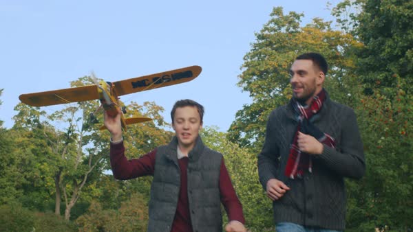 Father and son are launching model airplane in the park while running towards camera, slow motion Royalty-free stock video