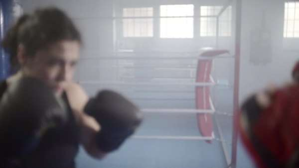 Young woman training with a coach in a boxing club, with a ring at background. Slow motion. Royalty-free stock video