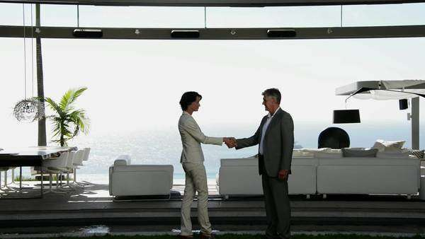 Mature businessman and businesswoman shaking hands in front of a luxury living room overlooking the sea. Royalty-free stock video