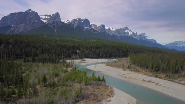 Aerial shot of a river winding nearby mountains Royalty-free stock video