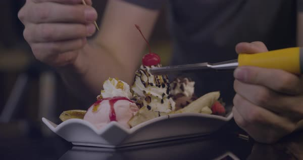 Slow motion shot of a man preparing a banana split with a chisel and a wooden skewer Royalty-free stock video