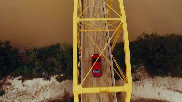 Aerial shot of a red car crossing a bridge Royalty-free stock video