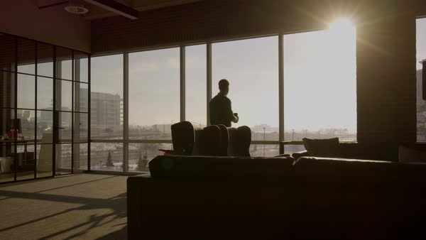 wide shot shot of businessman drinking coffee in office Rights-managed stock video