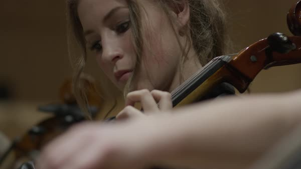 Close up panning shot of students playing cellos in orchestra Rights-managed stock video