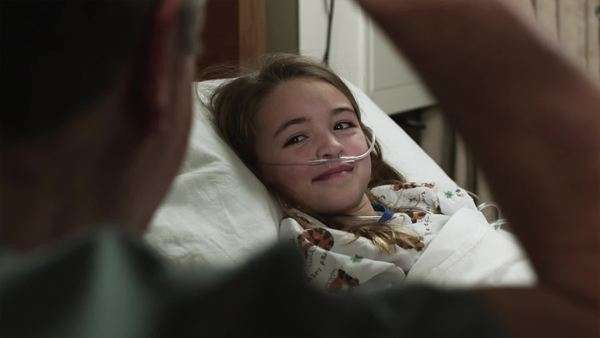 Close-up of girl lying in hospital bed being visited Royalty-free stock video