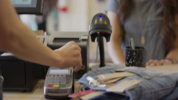 Close up panning shot of cashier swiping credit card for customer in store Royalty-free stock video