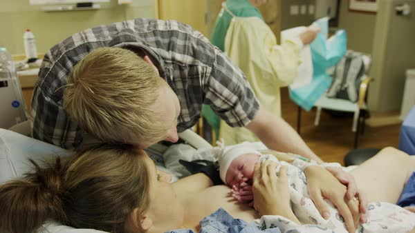Medium high angle shot of parents admiring newborn baby in hospital Rights-managed stock video
