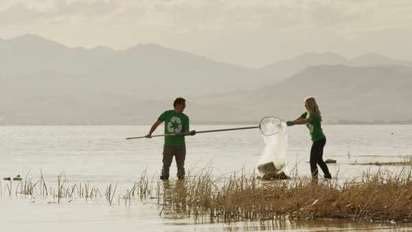 Wide panning shot of volunteers scooping garbage from lake Royalty-free stock video