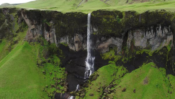 Wide panning shot of waterfall flowing over cliff Rights-managed stock video