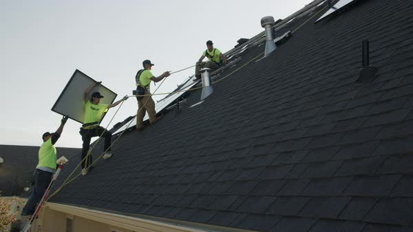 Wide panning low angle shot of workers carrying solar panel on roof Royalty-free stock video