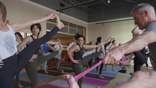 Medium slow motion panning shot of yoga class standing on one leg Royalty-free stock video