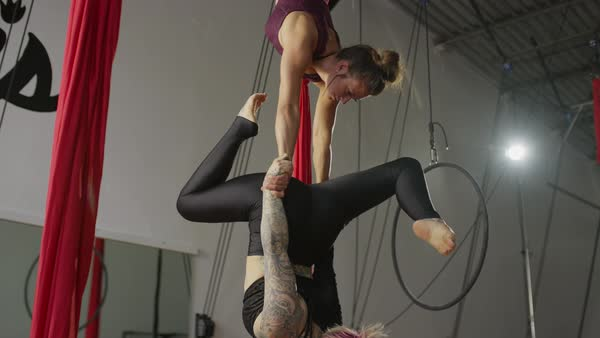 Medium panning shot of women hanging on aerial silks Rights-managed stock video