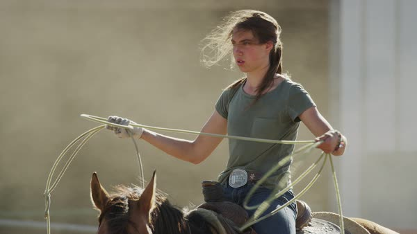 Medium slow motion shot of girl on horse holding lasso Rights-managed stock video