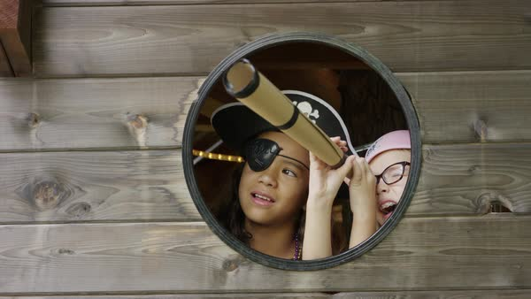 Close up of girls playing pirate in window using telescope / Provo, Utah, United States Royalty-free stock video