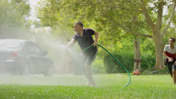 Boy with garden hose spraying friends running in grass / Provo, Utah, United States Royalty-free stock video