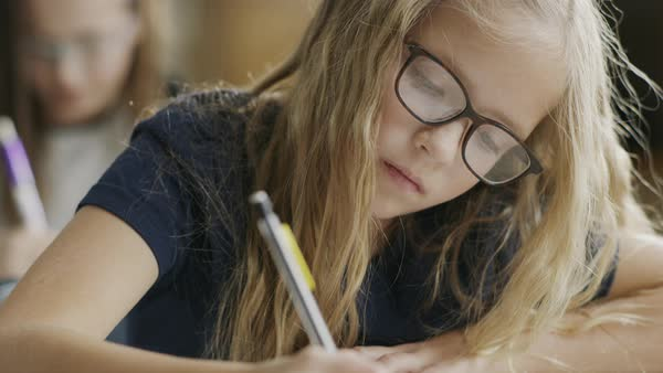 Pan up to girl writing on test at desk in classroom Royalty-free stock video