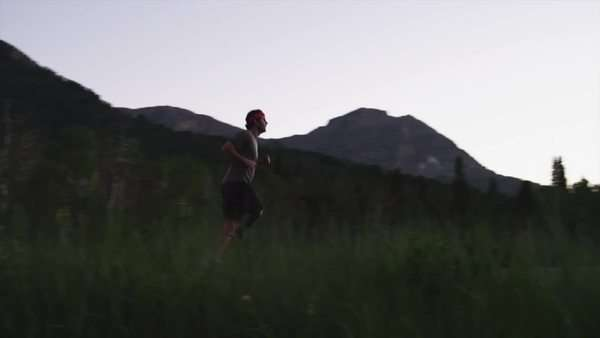 Wide shot pan disabled athlete with artificial limb jogging in mountains at sunset / American fork Canyon, Utah, USA Rights-managed stock video