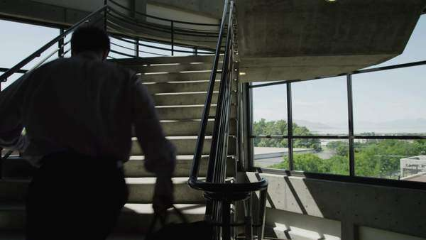 Wide shot tilt-up of Man running up office stairs, Utah Royalty-free stock video