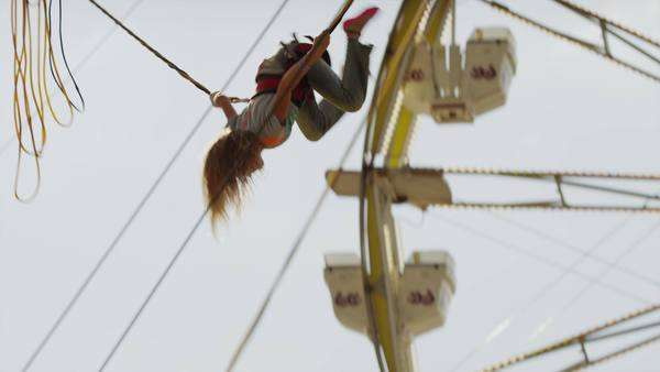 Medium panning shot of girl on bungee trampoline at amusement park / Salt Lake City, Utah, United States Royalty-free stock video