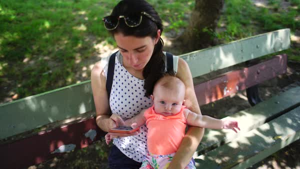 Medium shot of a woman using her phone while holding her child Royalty-free stock video