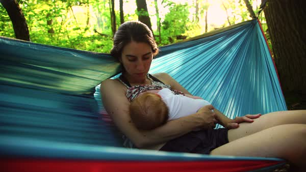 Medium shot of a mother breastfeeding her baby in a hammock Royalty-free stock video