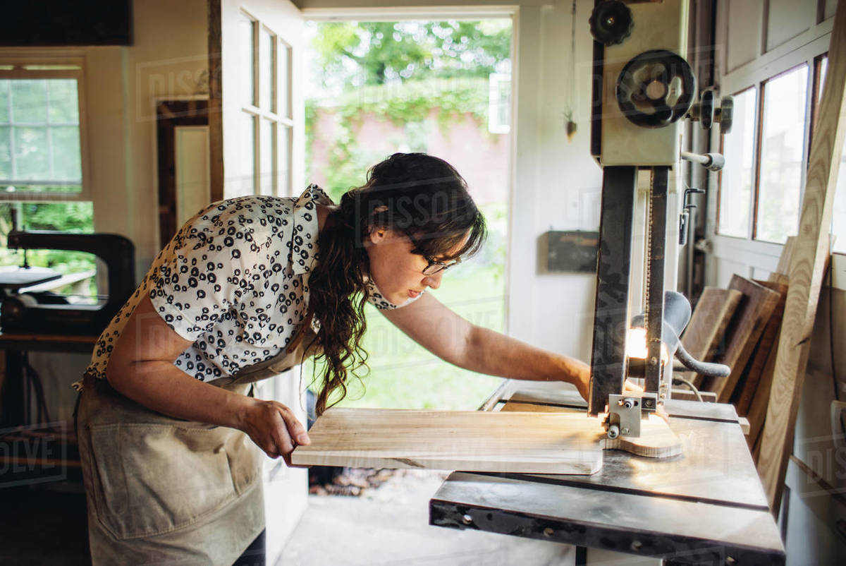 Female carpenter working with piece of timber on wood cutting machine in workshop Royalty-free stock photo