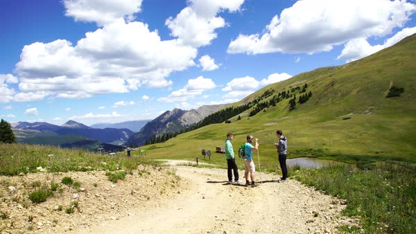 Wide shot of three hikers standing on a trail in the mountains Royalty-free stock video