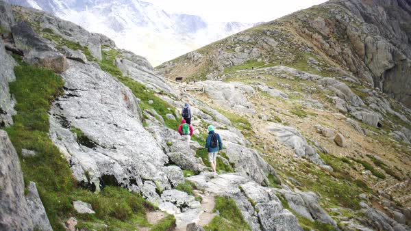 Wide shot of three hikers walking on a rocky slope Royalty-free stock video