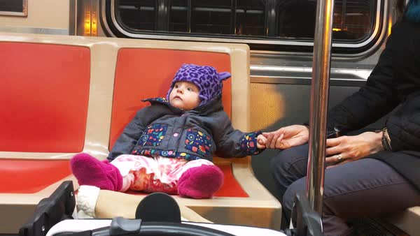Hand-held shot of a baby and her mother sitting in a subway train Royalty-free stock video