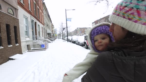 Mother walking with baby on a street in winter Royalty-free stock video