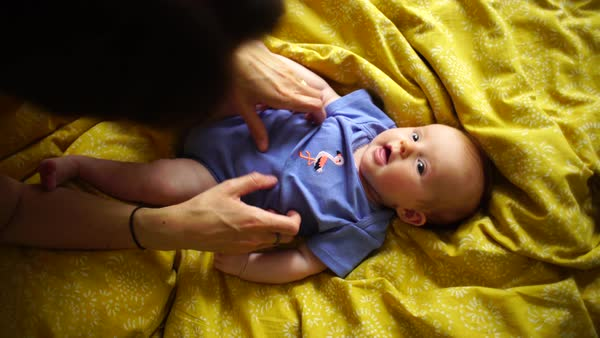 Medium shot of a woman playing with her baby girl in a bed Rights-managed stock video
