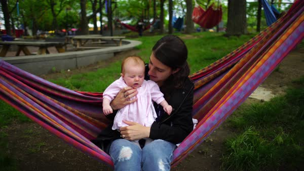 Medium shot of a woman holding her baby girl in a hammock Rights-managed stock video