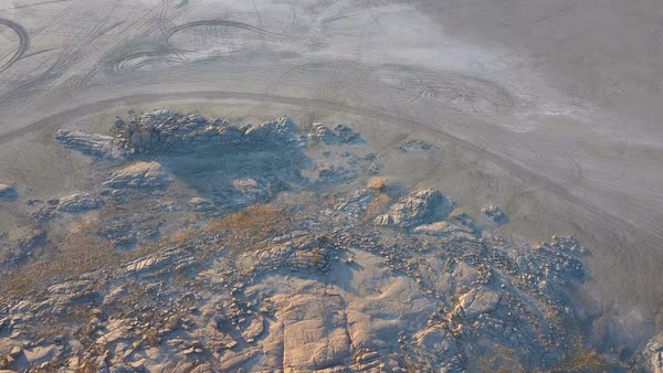 Transition from rocky outcrop to barren salt pan aerial shot Royalty-free stock video