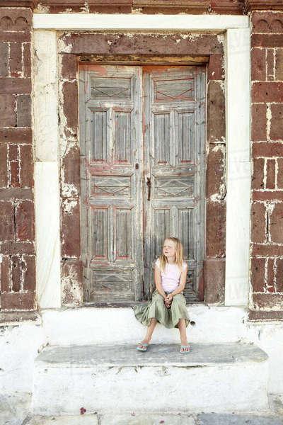 200ef23fba99 Girl sitting in front of wooden door Royalty-free stock photo