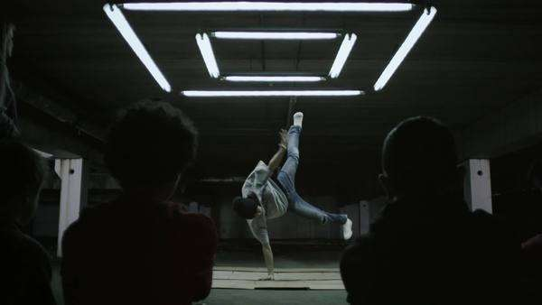 Dolly shot of B-Boy dancing under moody light, slow motion Royalty-free stock video
