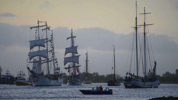 old sailing ships sailing down and up the river in the evening