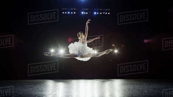 Rear view of serious ballet dancer leaping in costume performing onstage in show Royalty-free stock photo