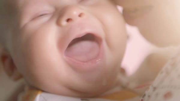 Close-up of baby's face while it smiles and laughs. Happy child in mother's hands. Royalty-free stock video