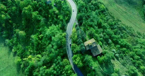 House in the forest next to the road on which cars drive. Aerial shot. Shooting from the top without moving Royalty-free stock video