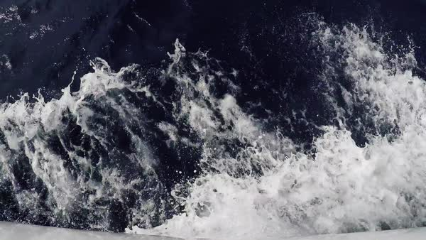 Foamy blue waves beat on the deck of the yacht. Water trail next to the yacht. Raging foamy waves of the blue clear sea, top view Royalty-free stock video