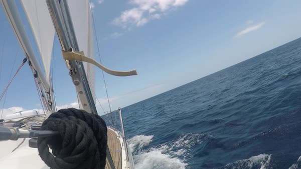 POV shot of a sailing yacht, boat. Sea voyage on a yacht with white sails. Luxury yacht cruising. Tourism, outdoor activities. View of part of the deck, black rope Royalty-free stock video