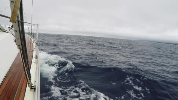 POV Journey on a yacht with sails down in cloudy weather. Waves hit the sea ship, splashing water. Sea view through the deck of the yacht. Endless blue sea, in the background the horizon line Royalty-free stock video