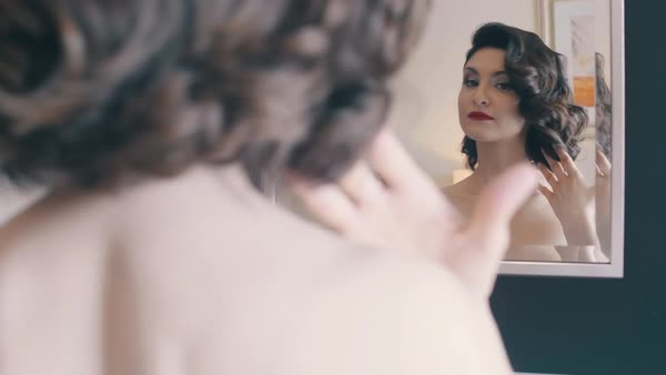 Woman with beautiful make-up and hairstyle admires herself, sitting in front of the mirror, slow motion. Over-the-Shoulder Shot. Medium Shot. Royalty-free stock video