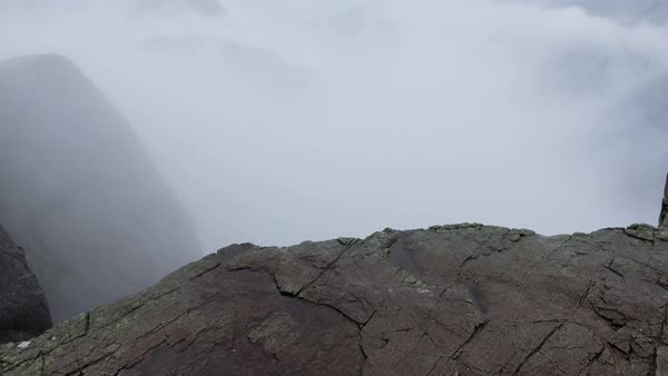 Someone, something approach the edge of abyss at high altitude, break off. Preikestolen Landscape, Prekestolen, Preacher's Pulpit, Pulpit Rock. Magnificent scenery, mountains, steep cliffs in the fog Royalty-free stock video