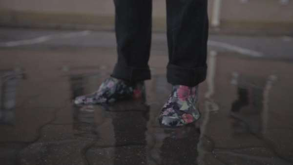 Legs in waterproof shoes stand in a puddle Royalty-free stock video